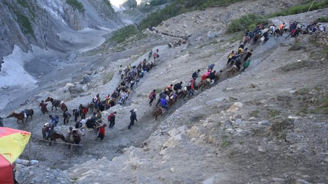 stockvideo's en b-roll-footage met hindu walk on mountain trails on foot ponies and are being carried in the palanquins as they make their pilgrimage to the sacred amarnath caves one... - bedevaart