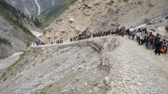 hindu walk on mountain trails on foot ponies and are being carried in the palanquins as they make their pilgrimage to the sacred amarnath caves one... - metric system stock videos and b-roll footage