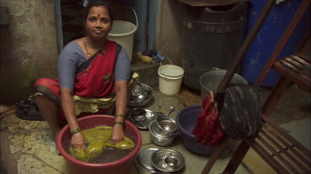 A Hindu woman washes her laundry in a bowl. Available in HD.