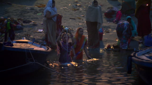 Hindu women bathe in the holy waters of the Ganges River in the city of Varanasi.