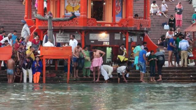 hindus bathing in the sacred waters of ganges / haridwar is an ancient city and important hindu pilgrimage site where the river ganges exits the... - acqua santa video stock e b–roll