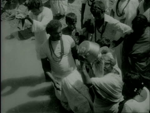 1977 B/W Hindus, gathered at a temple, put themselves through religious cleansing of sins rituals at a river and by walking barefoot through fire / Durban, South Africa