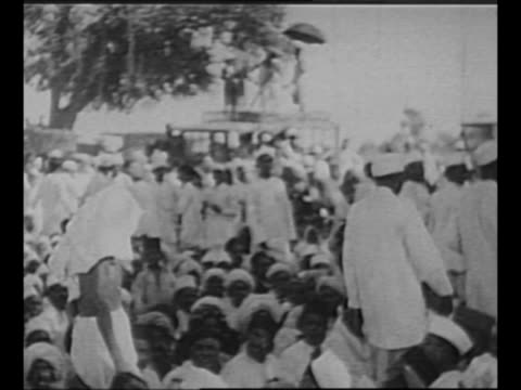 stockvideo's en b-roll-footage met hindus walk on sidewalk / montage indian political leader mohandas k. gandhi walks / men on platform wave for others to approach as other men prepare... - mahatma gandhi