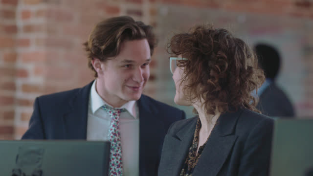 hip businesswoman laughs, is interrupted by coworker who joins in the conversation - formal businesswear stock videos & royalty-free footage