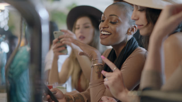 stockvideo's en b-roll-footage met hip, diverse young women look at smartphone and laugh as they chat over drinks at crowded bar. - scrolling