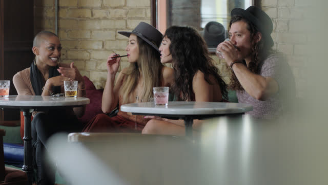 vidéos et rushes de hip group of friends chat while drinking cocktails and smoking electronic cigarette at happy hour in austin bar. - fumer du tabac