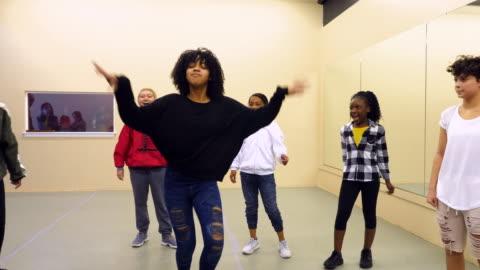 ms hip hop dance group watching female teammate perform during practice in dance studio - girls stock videos & royalty-free footage
