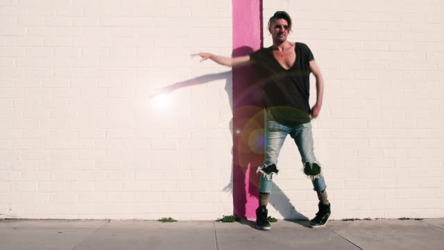 hip man in torn jeans dancing in front of white wall - hüfte stock-videos und b-roll-filmmaterial
