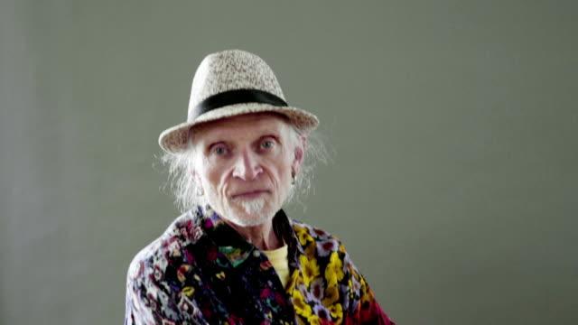 hip senior gay man in a colourful shirt - kopfbild stock-videos und b-roll-filmmaterial