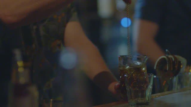 stockvideo's en b-roll-footage met hip young bartender stirs craft cocktail with swizzle stick. - cocktail