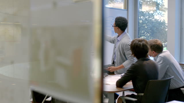 Hip young businessman points out numbers on white-board, leads meeting in office conference-room (dolly shot)