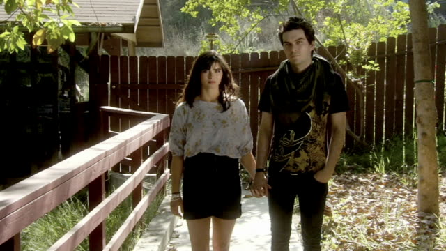 ms portrait hip young couple holding hands and looking at camera as they stand in front of wooden  fence/ los angeles, california - ausdruckslos stock-videos und b-roll-filmmaterial