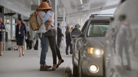 hip young couple playfully embrace and kiss as boyfriend arrives at ground transportation. - homecoming stock videos & royalty-free footage