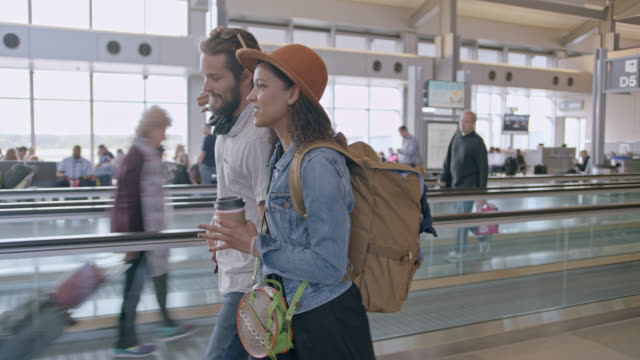 Hip young couple walks with arms around each other through airport terminal. Tracking.