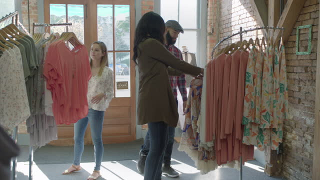 Hip young customers look around at clothes on display in modern brick and mortar retail shop.