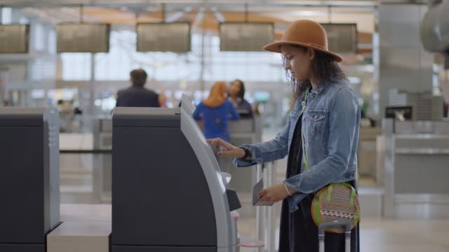Hip young female traveler checks in using kiosk, scans passport.