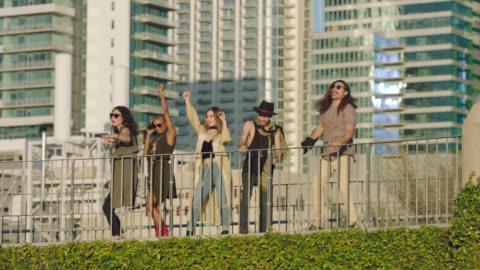 vídeos y material grabado en eventos de stock de slo mo. hip young friends laugh and dance with downtown austin, texas city skyline in background. - hípster urbano