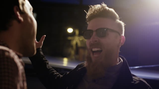 MS SLO MO. Hip young man in sunglasses greets friends and laughs at rooftop party.