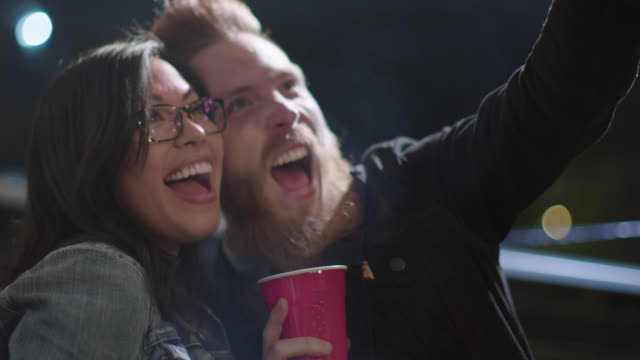 ms slo mo. hip young man smiles and poses for smartphone selfie with girl at rooftop party. - cool und lässig stock-videos und b-roll-filmmaterial