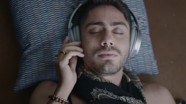 cu. hip young middle eastern man listens to music in headphones while resting head on pillow with his eyes closed. - eyes closed stock videos & royalty-free footage