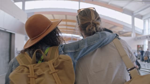 vidéos et rushes de hip young mixed-race woman walks with arm around boyfriend through airport terminal. pan around. - arrivée