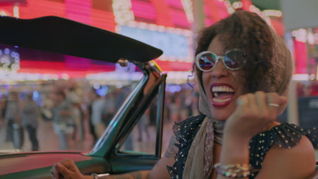 stockvideo's en b-roll-footage met hip young woman dances and sings in classic convertible on fun night out in downtown las vegas. - weekend activiteiten