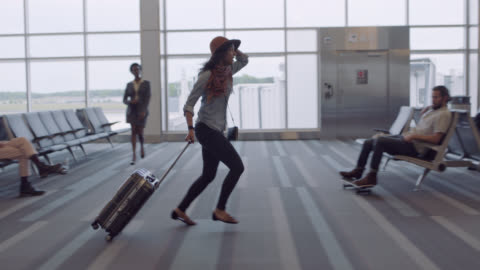 hip young woman frantically runs through airport waiting area, leaps over suitcase. - hüfte stock-videos und b-roll-filmmaterial