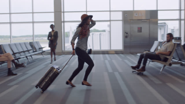 hip young woman frantically runs through airport waiting area, leaps over suitcase. - rennen körperliche aktivität stock-videos und b-roll-filmmaterial