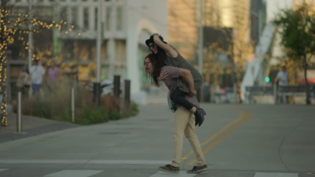 vídeos de stock, filmes e b-roll de slo mo. hip young woman jumps on boyfriend's shoulders for a piggyback ride as they cross a city street in downtown austin, texas. - feito pelo homem