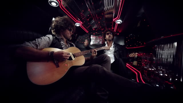 hip-hop artist dances while rocker jams on acoustic guitar in limousine at awards show - music video stock videos & royalty-free footage