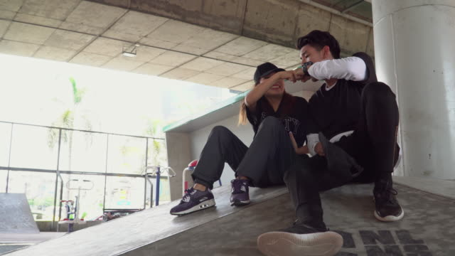 Hip-hop young couple fist bumping