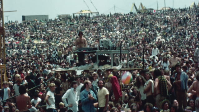 ws shaky pan hippie audience at woodstock festival, colorful beach ball bouncing above crowd / bethel, new york, usa - 1969年点の映像素材/bロール