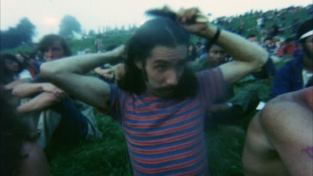 vídeos de stock e filmes b-roll de ms hippie audience at woodstock festival, man brushing hair in foreground / bethel, new york, usa - 1969