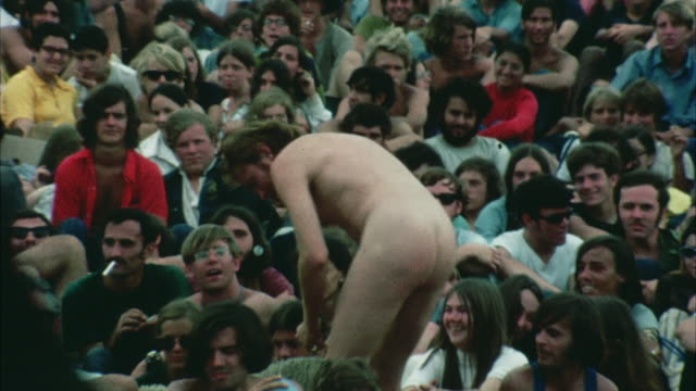 montage hippie audience at woodstock festival, naked man carrying sheep and placard against killing animals / bethel, new york, usa - anno 1969 video stock e b–roll