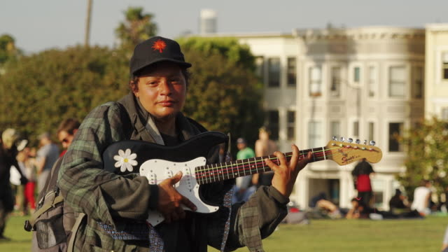 hippie band plays music in dolores park, san francisco usa - ギター点の映像素材/bロール