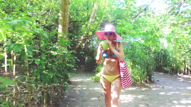 Hippie blonde woman walking and exploring jungle while drinking coconut juice, Maldives