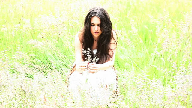 Hippie chick in a field picking long grass.