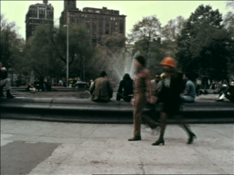 1969 profile hippie couple holding hands walking past fountain in washington square park / nyc - greenwich village stock videos & royalty-free footage