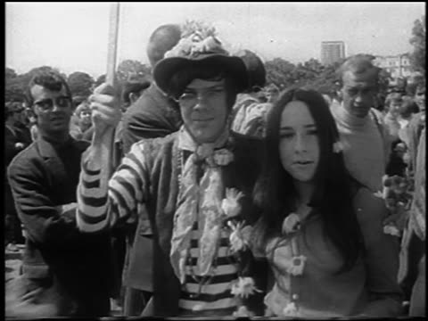 b/w 1967 hippie couple looking at camera as they walk past at bein / hyde park london / newsreel - hyde park london stock videos & royalty-free footage