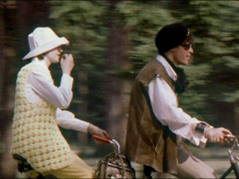 1970 hippie couple riding tandem bicycle down street - 小背心 個影片檔及 b 捲影像