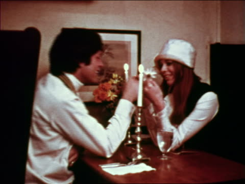 1969 hippie couple sitting at table by candlelight in restaurant / greenwich village, nyc - お食事デート点の映像素材/bロール