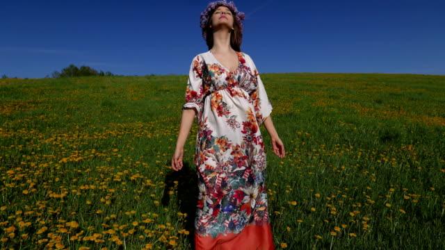 Hippie-Mädchen in einem Boho Kleid gekleidet geht über das Feld.