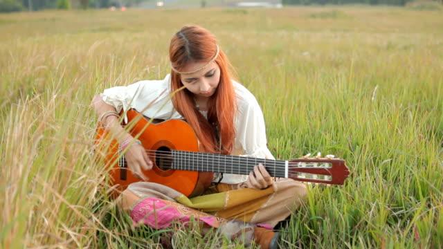 Hippie-Mädchen spielt Gitarre auf dem Rasen