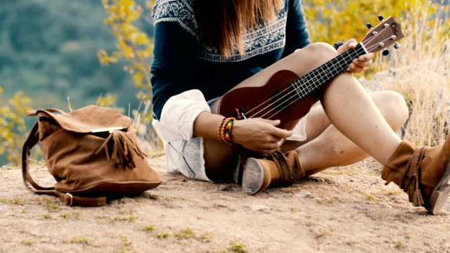 Hippie girl playing ukulele