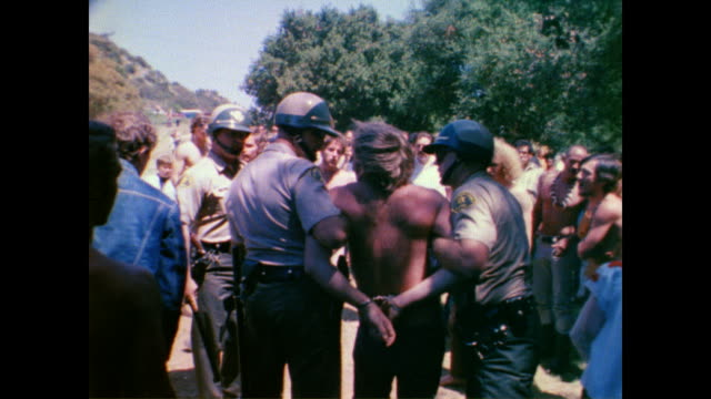 vídeos de stock e filmes b-roll de / hippie man being arrested at tapia park lovein / police handcuff man while he lies on the ground / crowd escort police as they walk through park /... - love in
