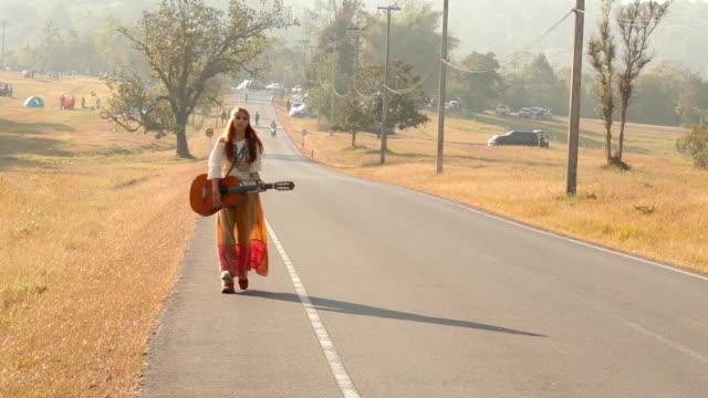 vídeos de stock, filmes e b-roll de hippie mulher caminhando na estrada - hippie
