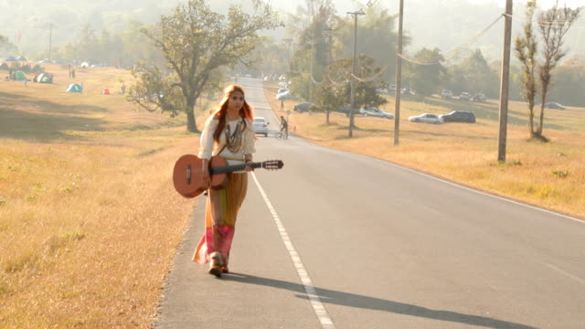 hippie woman walking on the road - folk music stock videos and b-roll footage
