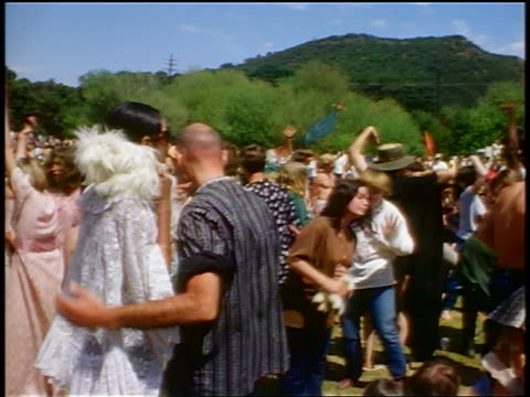 vídeos de stock e filmes b-roll de 1968 hippies dancing at outdoor concert / couple with dog walking thru crowd / jump cut / ca - love in