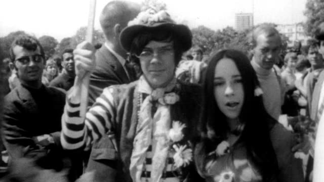vídeos de stock e filmes b-roll de hippies gather in hyde park to preach love peace and the legalization of marijuana / hippies in flowered hats dresses and with placards / man smoking... - hippie