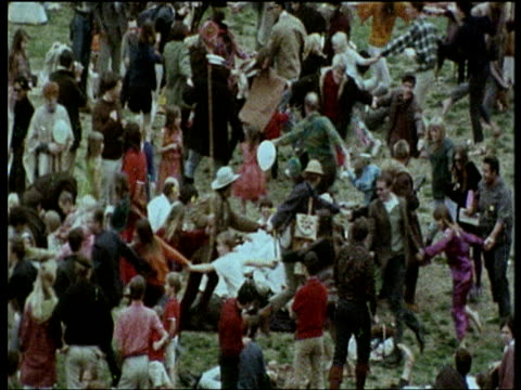 vídeos de stock e filmes b-roll de hippies making human chain by holding hands run around park zoom out to crowds of hippies at love in 1967 - hippie